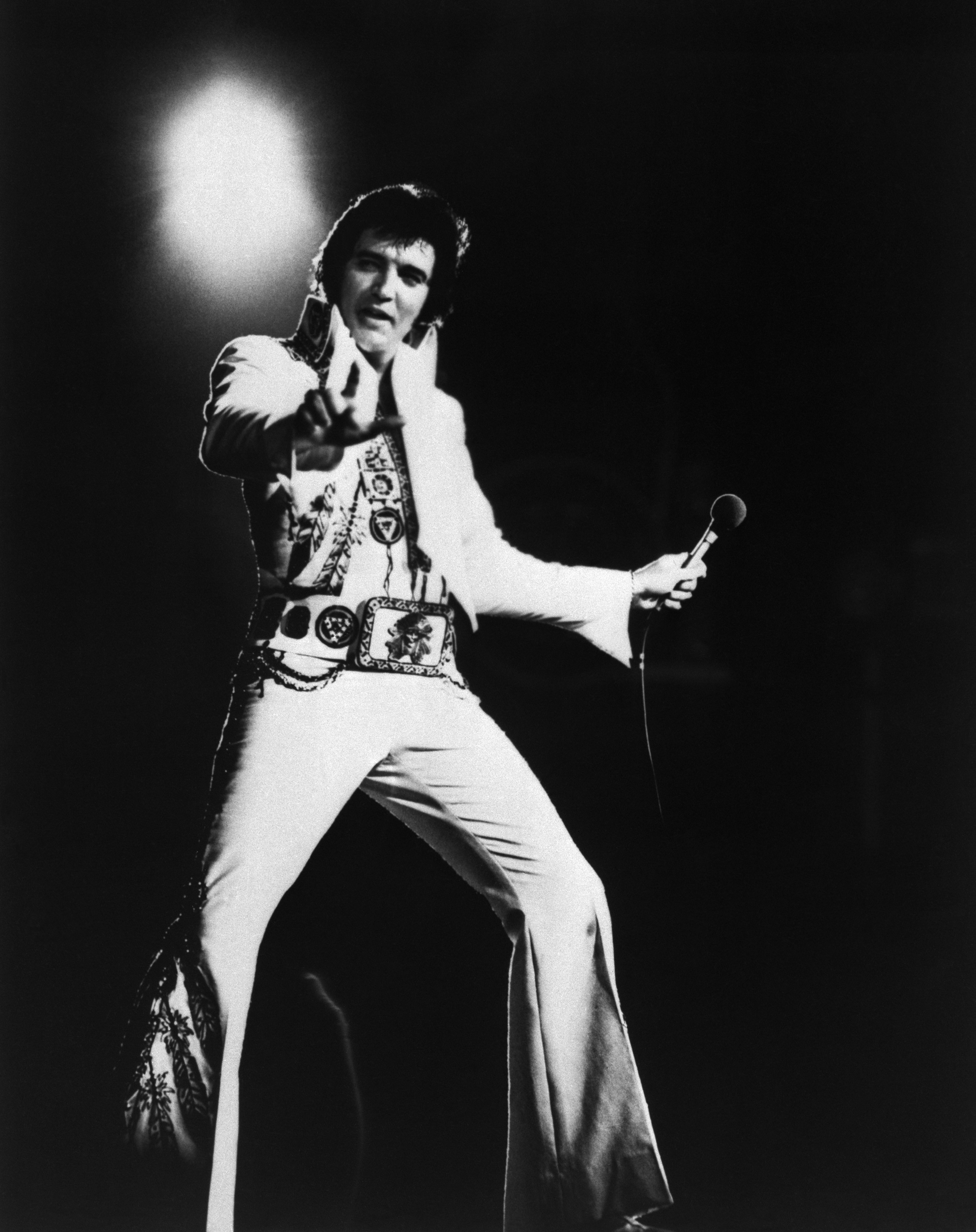 Elvis Presley strikes a pose during a 1977 concert, filmed for a television special, wearing one of his trademark jeweled white jumpsuits.